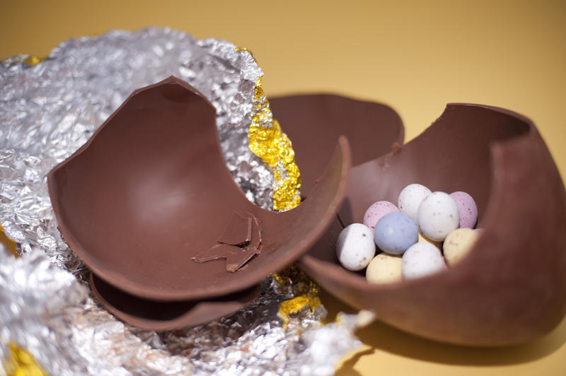 Broken pieces of a large chocolate Easter Egg with small sugar candy eggs inside.