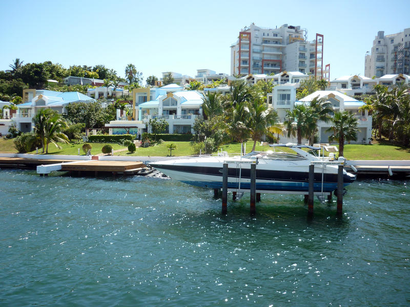 a luxury motor boat on a boat lift out the front of a somewhat ugly waterfront home - not proiperty released