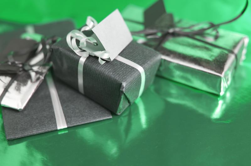 a trio of wrapped chritmas presents on a green coloured reflective background