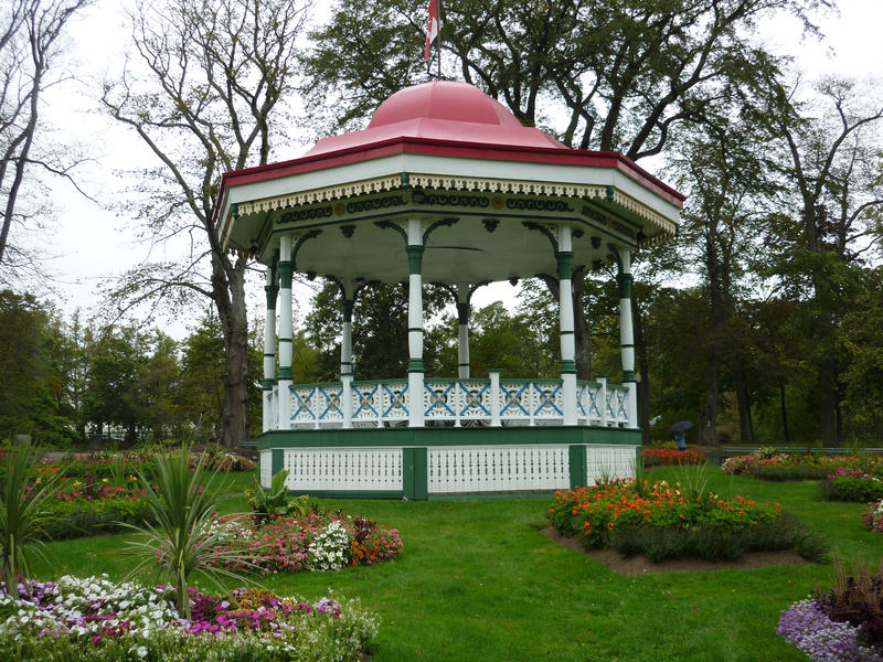 Pretty white painted bandstand or garden gazebo with a domed roof on a green lawn amongst pretty flowerbeds in a formal garden