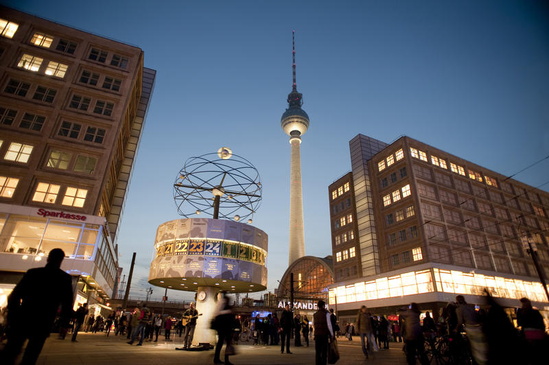 Nighttime view of crowds of people in the Alexanderplatz, Berlin with the International World Clock in the foreground and landmark Berlin TV tower behind
