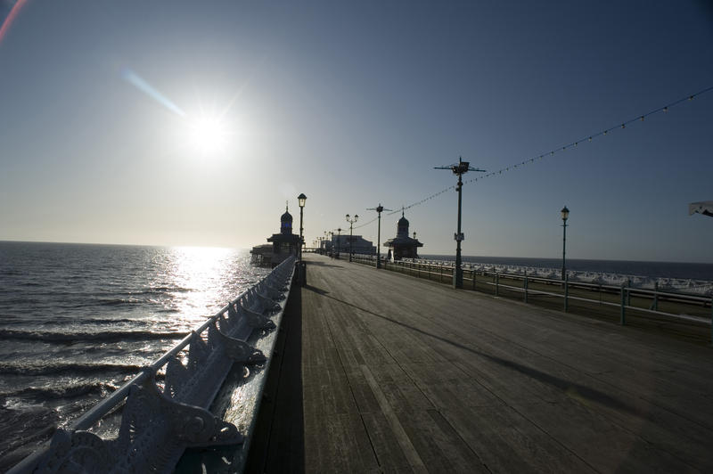 View along the deserted wooden broadwalk on Blackpool North Pier facing into the setting evening sun