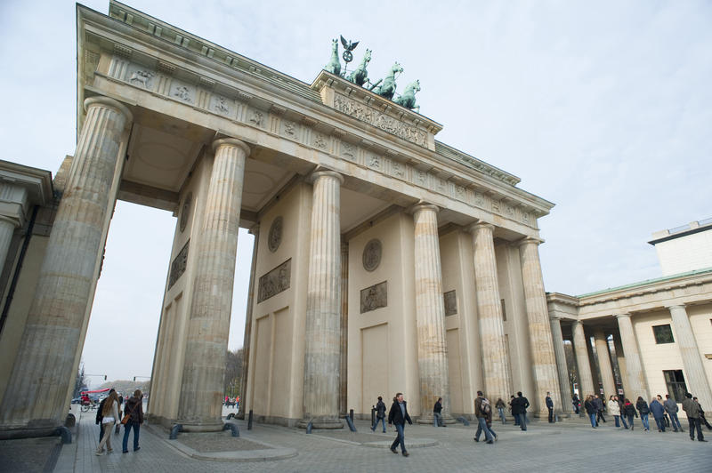 Low angle daylight view of the Brandenburg Gate, Berlin, with pedestrians in the foreground