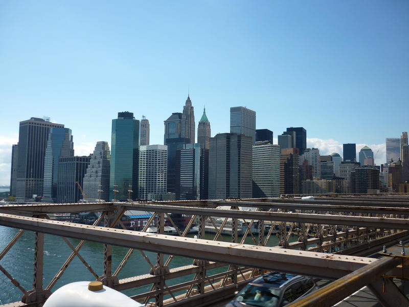 View of the skyscrapers of downtown Manhattan from Brooklyn Bridge under a clear blue sunny sky