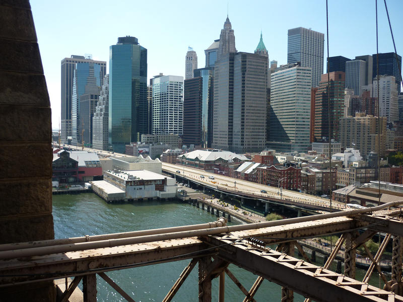 View of the Manhattan waterfront skyscrapers against a blue sunny sky from Brooklyn Bridge with a section of the framework in the foreground