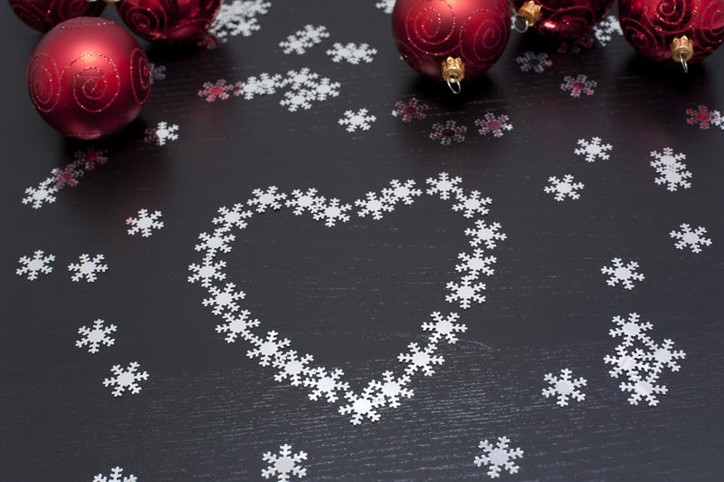Christmas snowflake heart decoration on a dark background with colourful red bauble ornaments