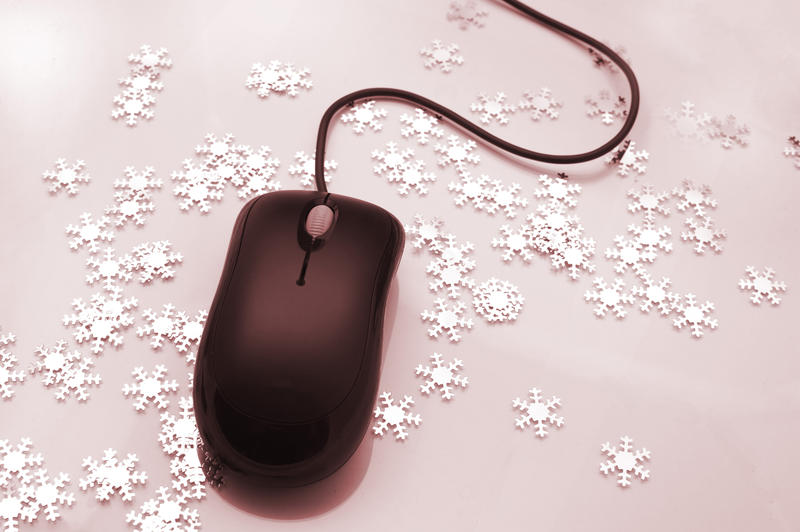 Computer mouse surrounded by scattered ornamental snowflakes conceptual of Christmas online shopping