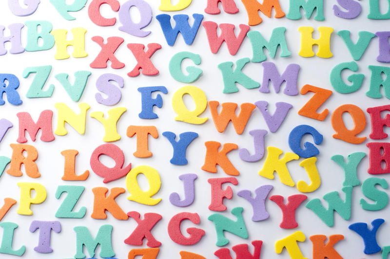 Colourful consonants background with uppercase alphabet letters scattered randomly over a white surface