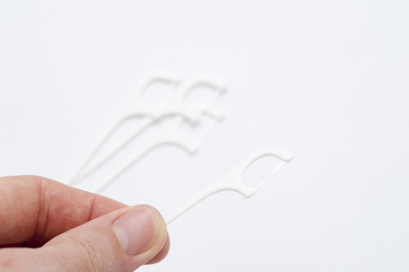 Man holding a disposable plastic flossing pick loaded with a length of dental floss for cleaning between his teeth