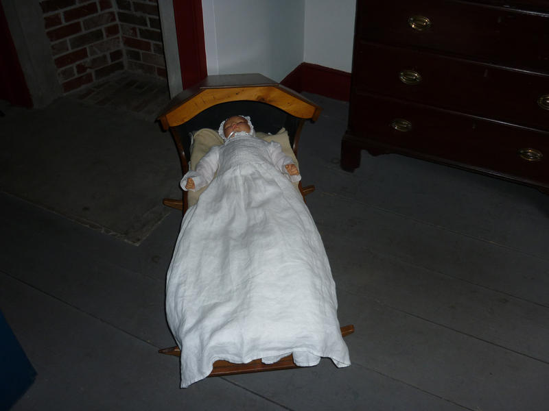 Antique doll lying in a wooden crib on an exhibit, view down the length of the crib