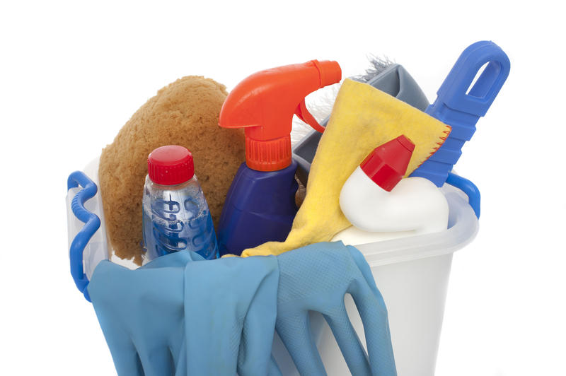 A studio shot over white of a bucket of domestic cleaning products with rubber gloves and sponges