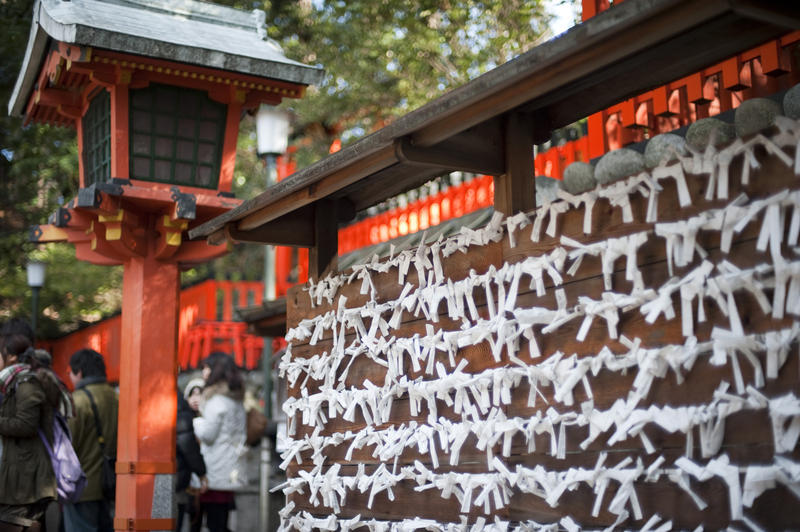 Omikuji placed by visitors to the Fushimi Inari Shrine (Fushimi Inari Taisha), Kyoto, japan