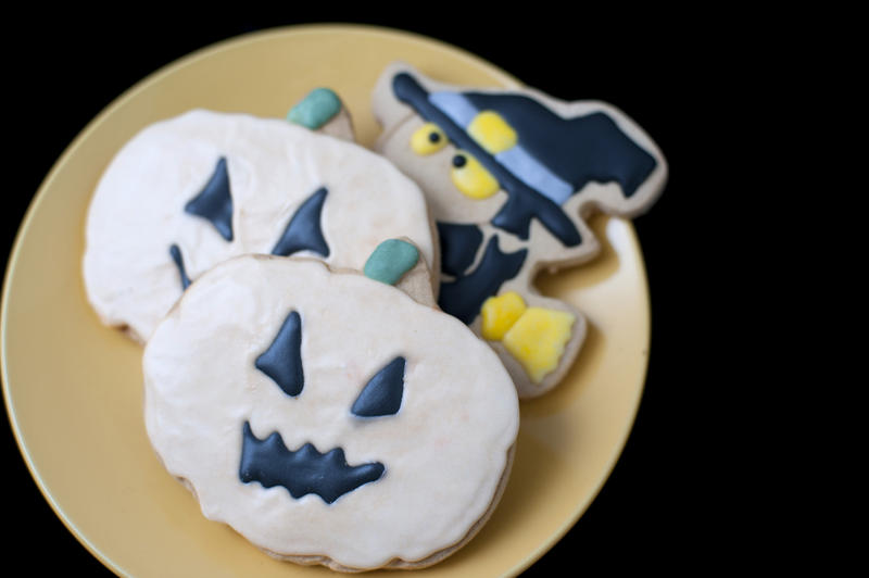 a place of halloween cookies decorated as a witch and pumpkins with icing