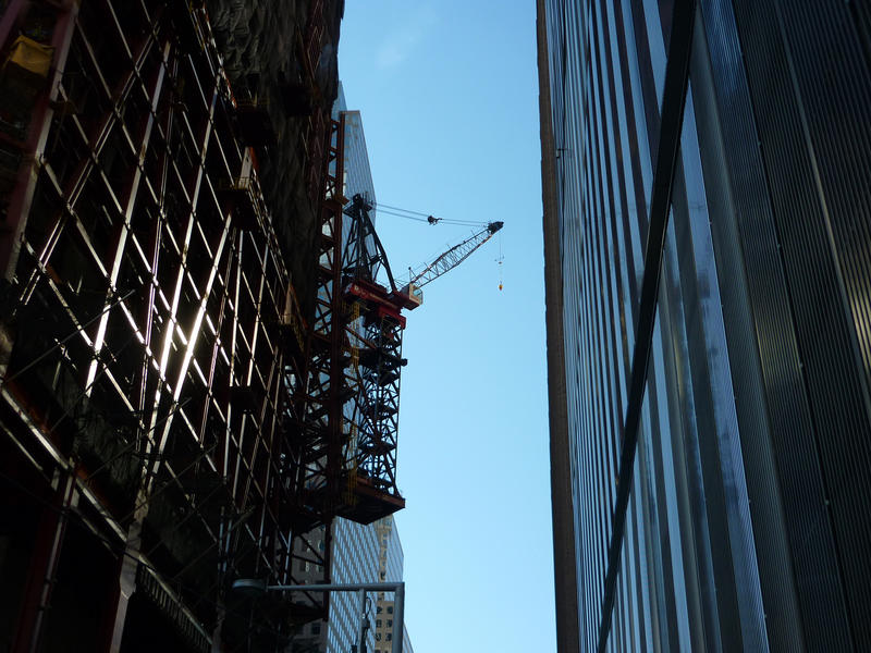 View looking upwards between highrise buildings on a narrow street to a crane suspended from a building facade that is still under constrcution and covered in scaffolding