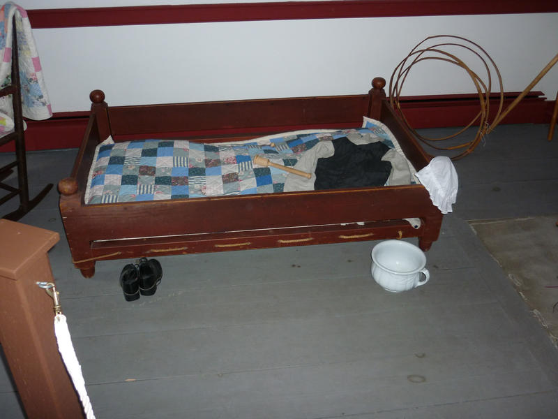Historic childs cot with a wooden frame and duvet with tiny boots, a night cap and potty in a museum exhibit