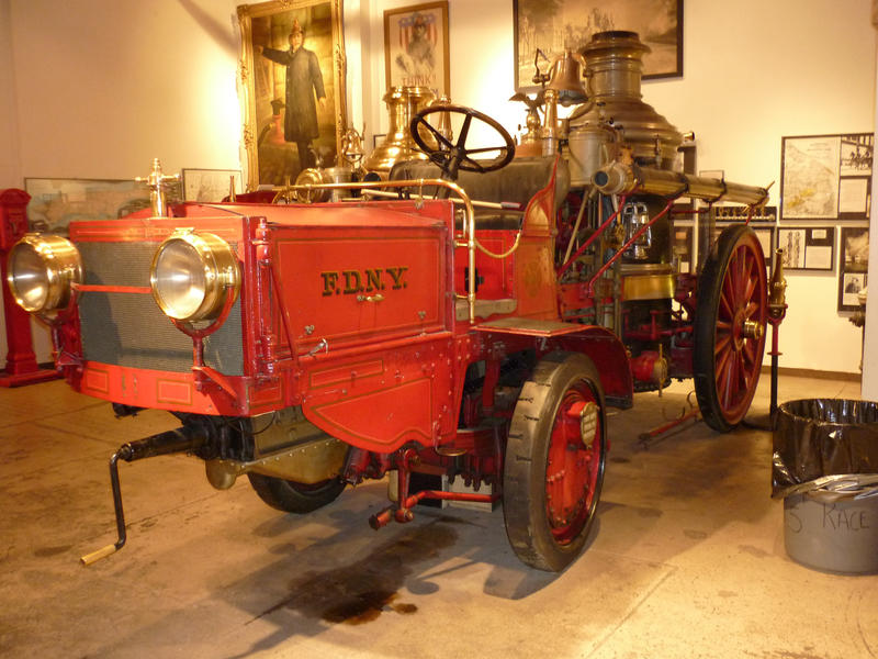 Historic red firetruck on display with a crank handle, steam engine and old spoked metal wheels