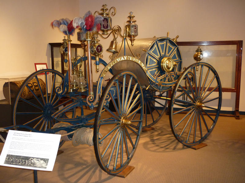 Beautiful nostalgic old historic horse-drawn fire wagon with brass coachwork and bell and a large reel mounted hose