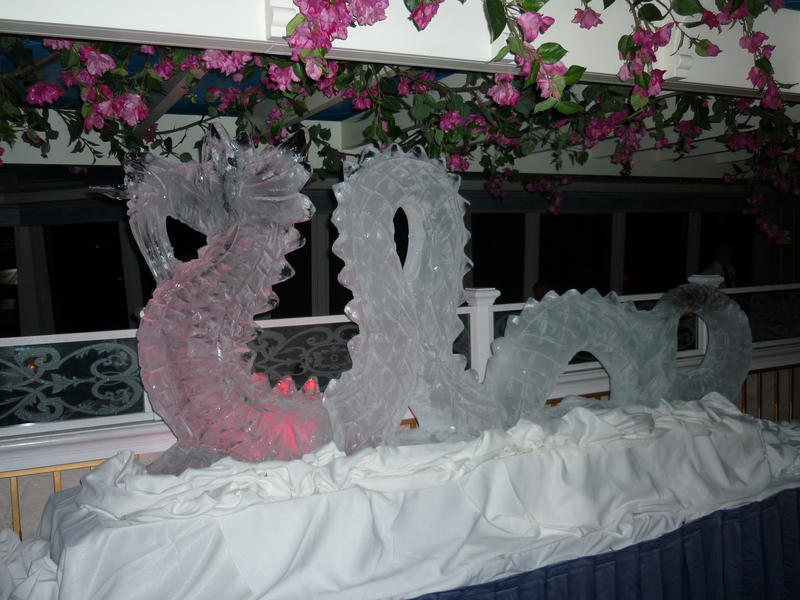 Sinuous ornately carved ice dragon sculpture on display surrounded by pink flowers