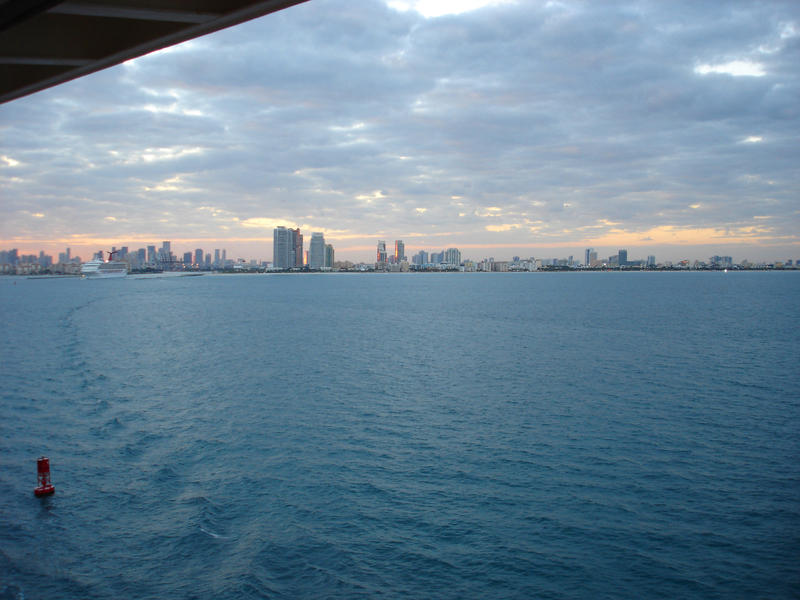 View from the deck of a luxury ship leaving Miami on a cruise of the cityscape on the horizon over open ocean