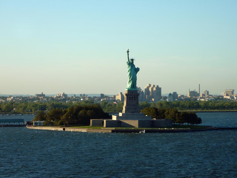 View from the ocean of the iconic Statue of Liberty on her small island against a clear blue sky, a gift from the French to the Americans