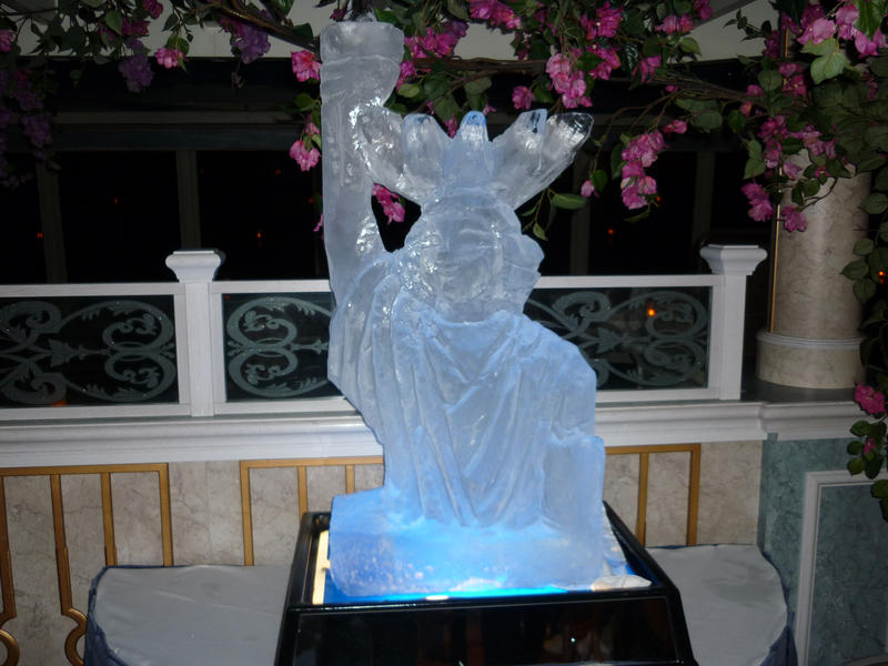 A bottom lit ice sculpture of the Statue of Liberty, with blue lighting