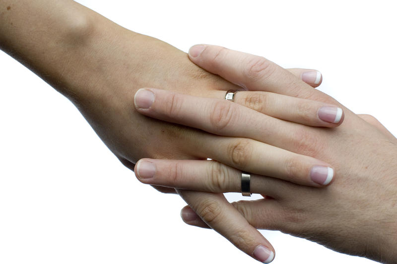 a romantic couple holding hands with fingers linked together