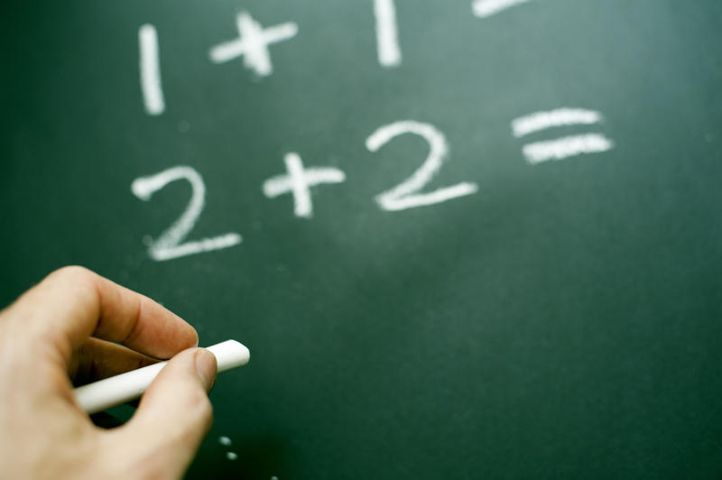 Teachers hand doing mathematics writing basic sums on a blackboard with chalk to teach kindergarten children addition and simple mathematics