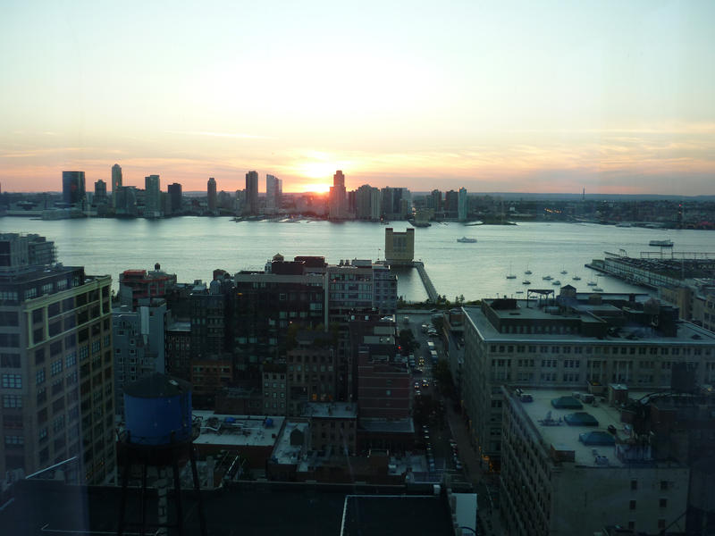 View over the East River of a glowing colourful sunset over New York with the skyscrapers silhouetted against the sky