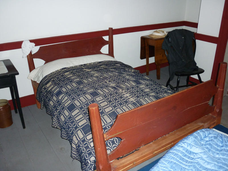 Double wooden bed with bedclothes and side tables in an empty hotel bedroom interior