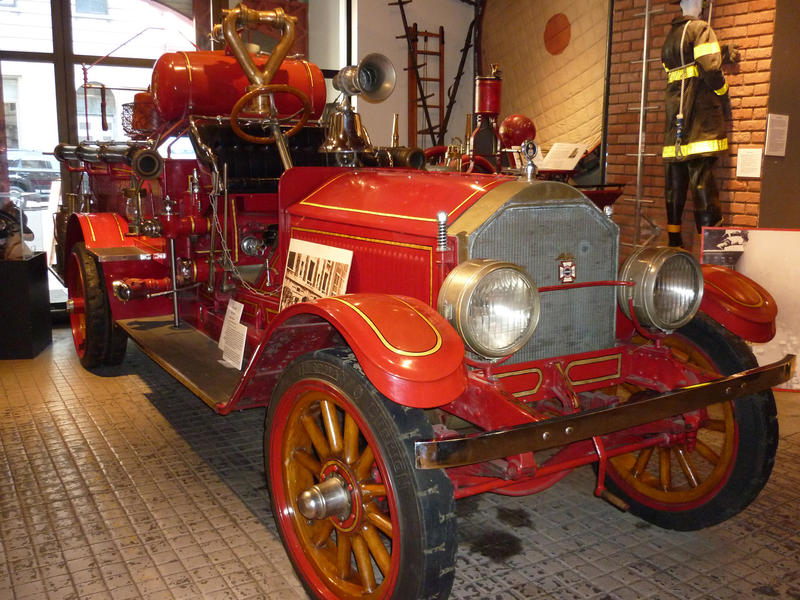 Beautifully restored historical vintage red firetruck on display in a showroom