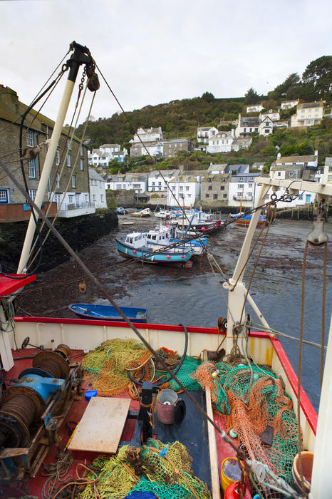 View of the harbour and traditional white-washed cottages in Polperro fishing village, Cornwall with a colourful collection of nets and equipment on the deck of a fishing boat in the foreground