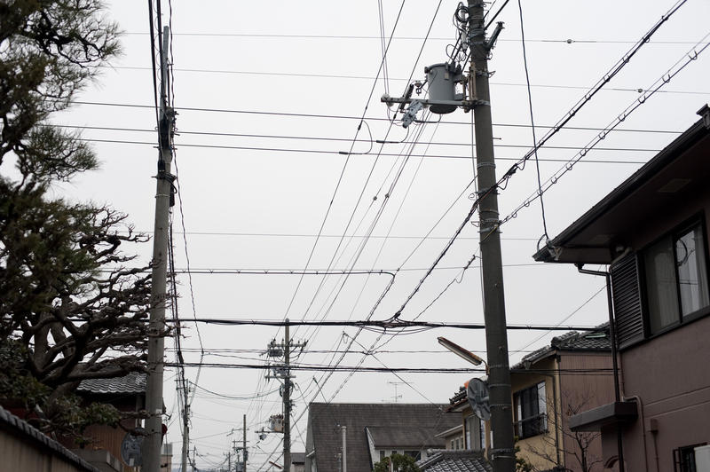 a common sight in japan, power and communications cables strung down the street from poles