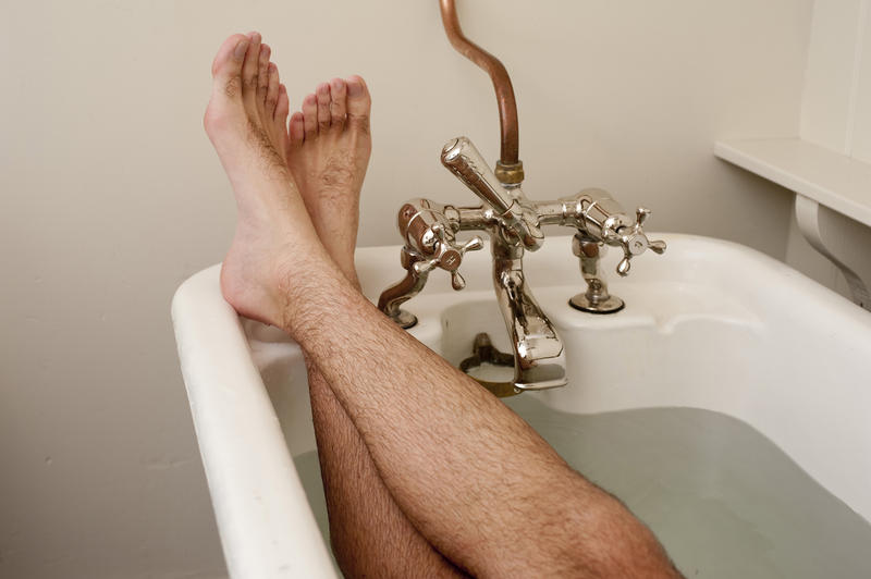 Crossed male feet in a relaxing position in a bathtub with old-fashioned faucet