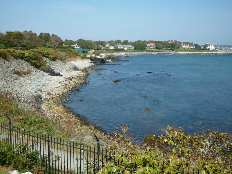 View of the Rhode Island coastline looking along a bay and beach towards waterfront properties in the distance