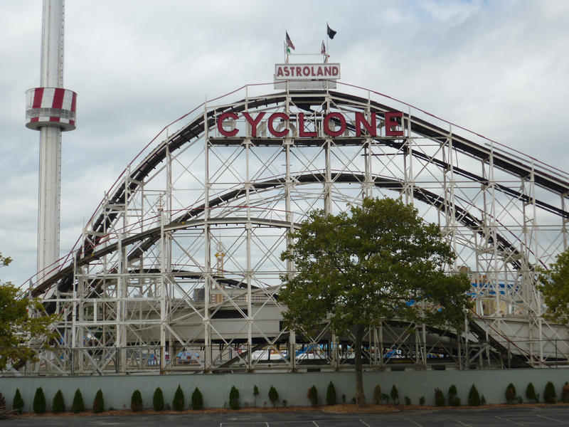Steel framework of the Cyclone rollercoaster ride at Astroland amusement park silhouetted against a cloudy blue sky