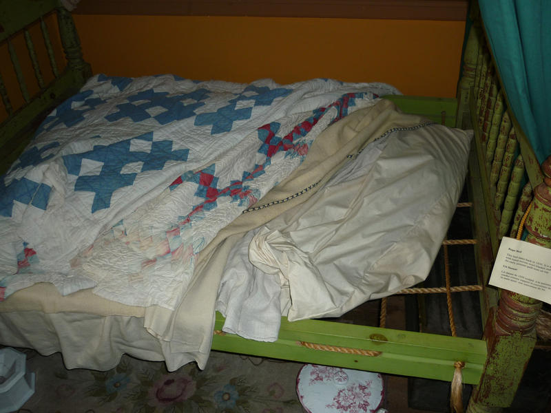 Small restored wooden antique country bed with rope supports for the bedclothes to lie on