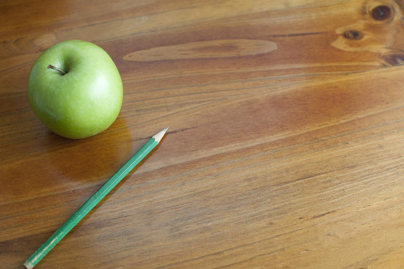 Schooled themed background of a wooden desk with a green apple and ... School Desk Background