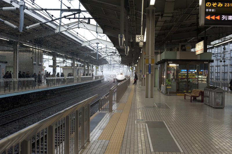 a shinkansen bullet train approaching a japanese railway station