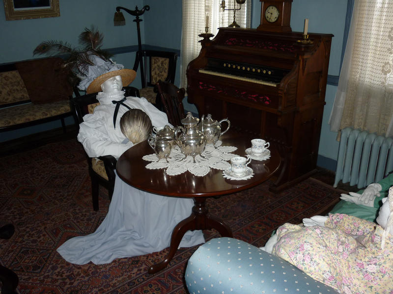 Museum exhibit of the interior of a Victorian or Edwardian parlour with a lady entertaing her friend with a silver tea service