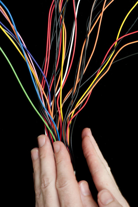 Splayed multiple brightly coloured electric wires converging between two human hands on a black background