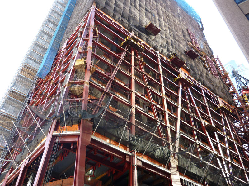 Detail of the construction of a skyscraper, showing the iron girder frame and scaffolding, taken from street level and looking up