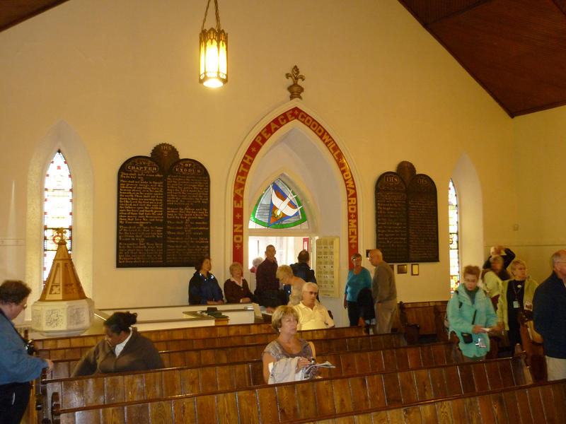 Interior of St George Church looking towards the door with members of the congregation entering and taking seats in pews