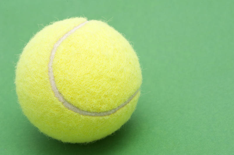 a single tennis ball on a green background