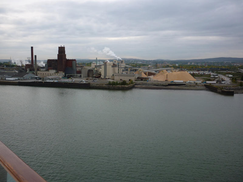 View across water to waterfront industrial buildings with chimneys releasing smoke into the air causing pollution, built near a waterway for ease of transport of manufactured goods