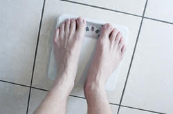 6897   Man weighing himself on a scale