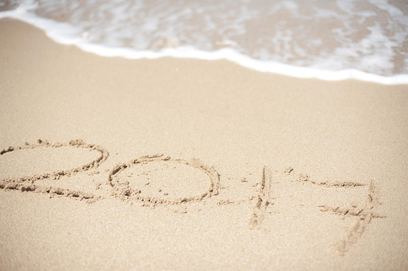 2017 seaside New Year greeting with the date hand drawn on the golden beach sand alongside the edge of the surf