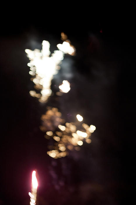 Abstract background of festive fireworks bursting in a colorful shower of sparks in a night sky, defocused blurred bokeh effect with copyspace