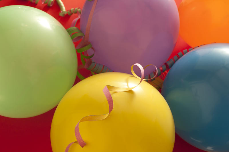 Party or celebration background of colorful balloons and spiral streamers in a close up full frame view from above