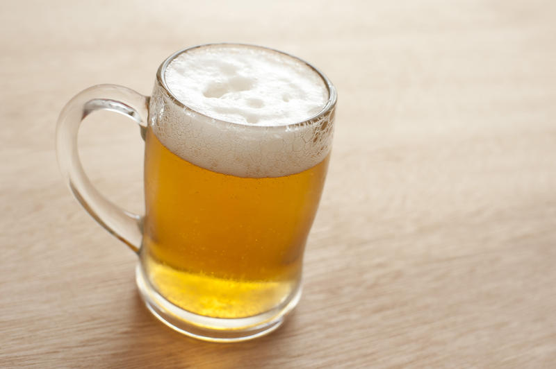 Glass tankard full of cold frothy beer standing on a wooden counter, high angle view with copyspace alongside