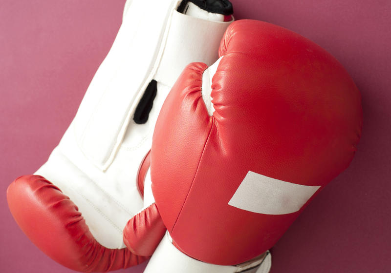 Close up White and Red Boxing Gloves for Fitness Workout on Dark Pink Background